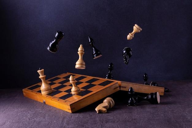 Échiquier et pièces d'échecs volantes sur fond sombre