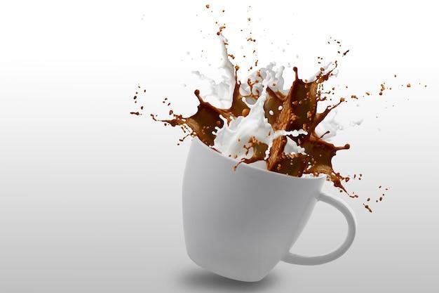 Éclaboussure de café et de lait dans une tasse blanche isolée sur blanc avec un tracé de détourage