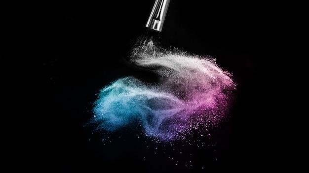 Éclaboussure de couleur poudre océan bleu et violet et pinceau pour le maquillage