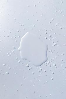 Une éclaboussure d'eau allumée sur la surface de la table blanche, des gouttes de pluie abstraites