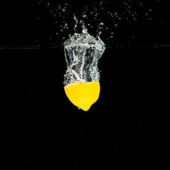 Éclaboussure de l'eau sur le citron coupé en deux sur fond noir