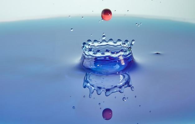 Éclaboussure d'eau de couleur abstrait, collision de gouttes colorées et création de couronne, art conceptuel avec effet abstrait.