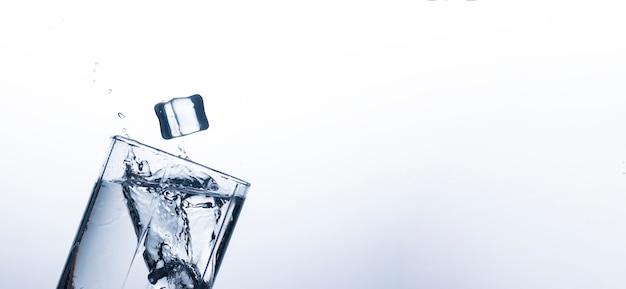 Éclaboussure d'eau dans un verre d'un glaçon. concept d'étancher la soif et de refroidir les boissons par temps chaud. bilan hydrique et consommation d'eau quotidienne. .