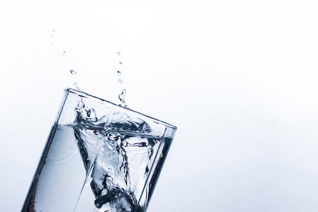 Éclaboussure d'eau dans un verre d'un glaçon.