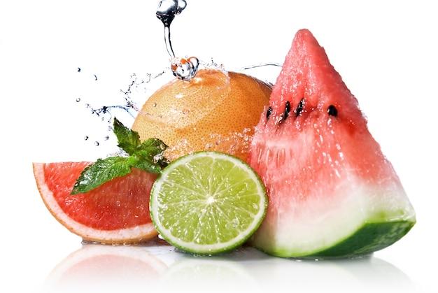 Éclaboussure d'eau sur les fruits frais isolés sur blanc
