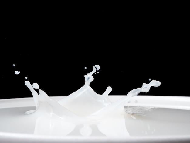 Éclaboussure de lait d'une tasse sur fond noir.