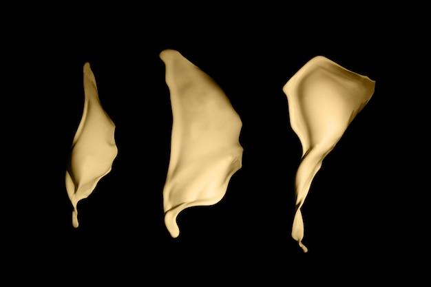 Éclaboussure de peinture dorée isolée sur fond noir.