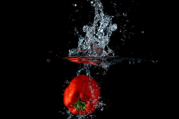 Éclaboussure de poivron rouge sur le mur noir de l'eau