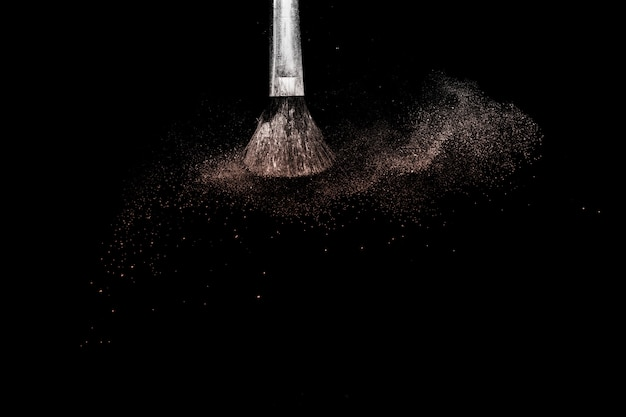 Éclaboussure de poudre et pinceau pour maquilleuse sur fond noir