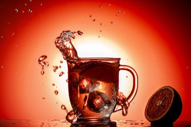 Éclaboussures dans un verre d'eau sur un fond coloré
