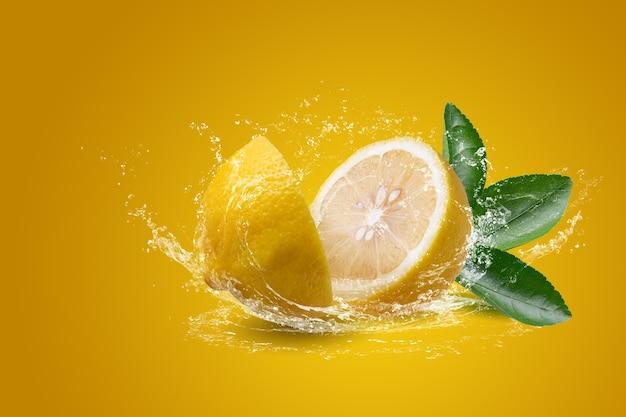 Éclaboussures d'eau sur des fruits de citron tranchés isolés sur fond jaune