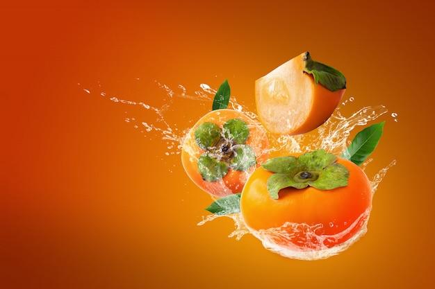 Éclaboussures d'eau sur des kakis frais sur fond orange