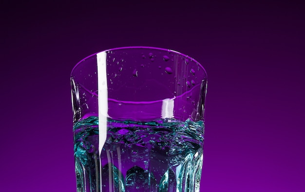 Les éclaboussures d'eau en verre sur fond lilas