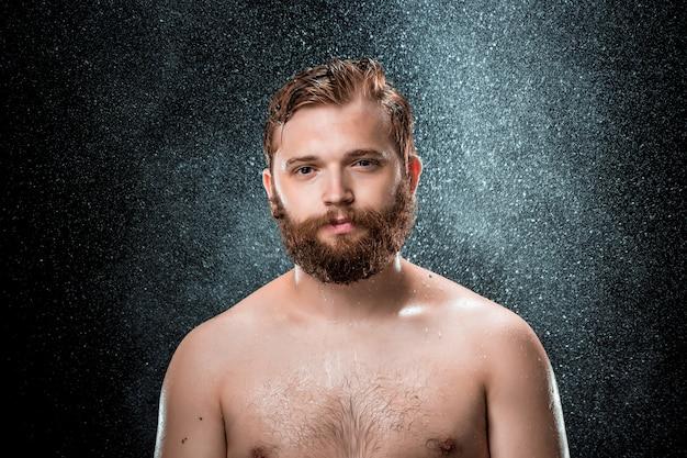 Les éclaboussures d'eau sur le visage masculin