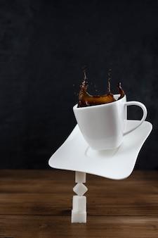 Éclaboussures et éclaboussures d'un morceau de sucre dans une tasse avec du café sur un fond en bois.