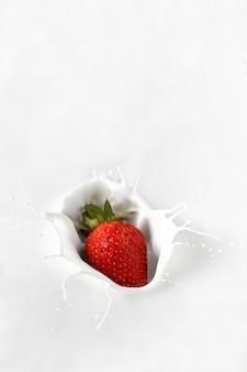 Éclaboussures de fraises dans du yogourt ou du lait fermer les baies par paquet