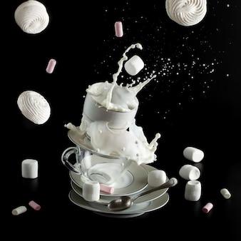 Éclaboussures de lait et lévitation de meringues sur fond noir. concept de petit déjeuner et collation.