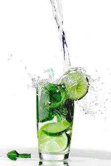 Éclaboussures de mojito cocktail au citron vert et menthe isolé sur fond blanc