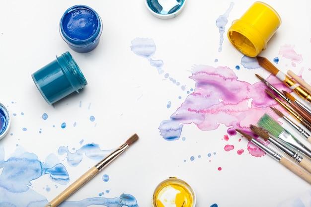 Éclaboussures de peinture aquarelle et fournitures de peinture se bouchent