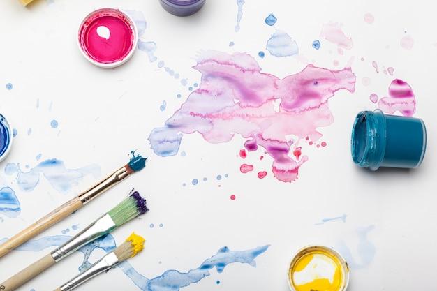 Des éclaboussures de peinture à l'aquarelle et des fournitures de peinture se bouchent