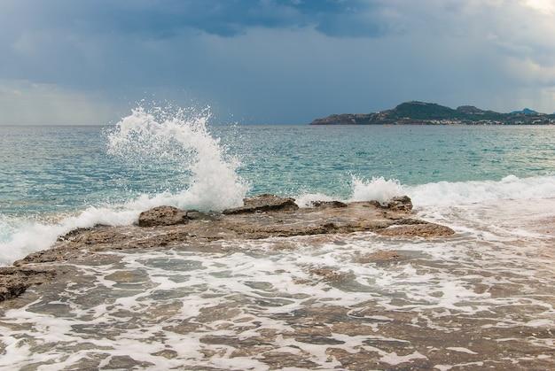 Éclaboussures de vagues sur des pierres sur la côte