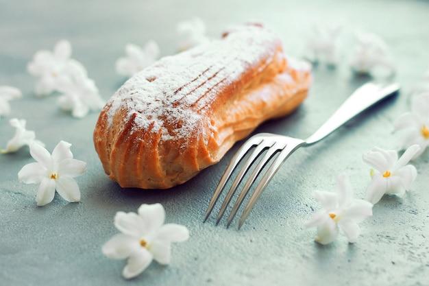 Eclair avec du sucre en poudre sur un fond gris, près d'une fourchette, des fleurs autour de la composition.