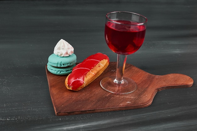 Eclair à la fraise avec macarons français et un verre de vin.