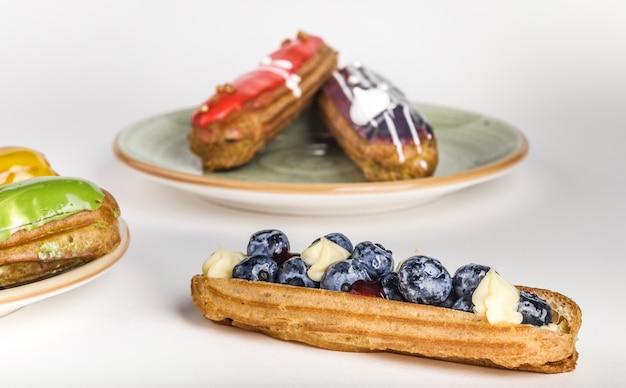 Eclair à la française avec crème de fruits et noix de coco et mousse douce. délicieux dessert. gâteau dans la glaçure. produit de confiserie.