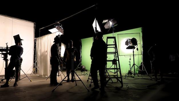 Éclairage discret de la silhouette de la production vdo dans les coulisses que l'équipe de tournage met en place