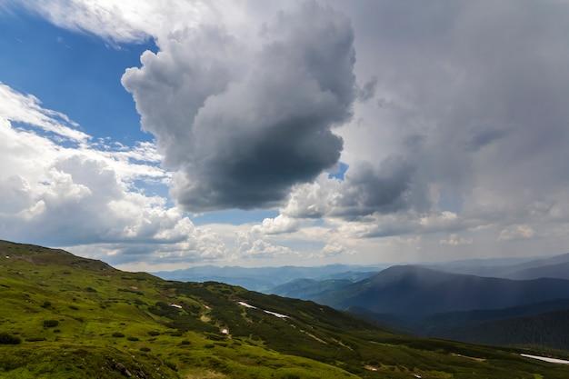 Éclairé par le soleil du matin, large vallée verte, collines couvertes de forêts et de montagnes brumeuses lointaines sous un ciel d'été bleu vif et des nuages blancs gonflés. beauté de la nature, du tourisme et du concept de voyage.