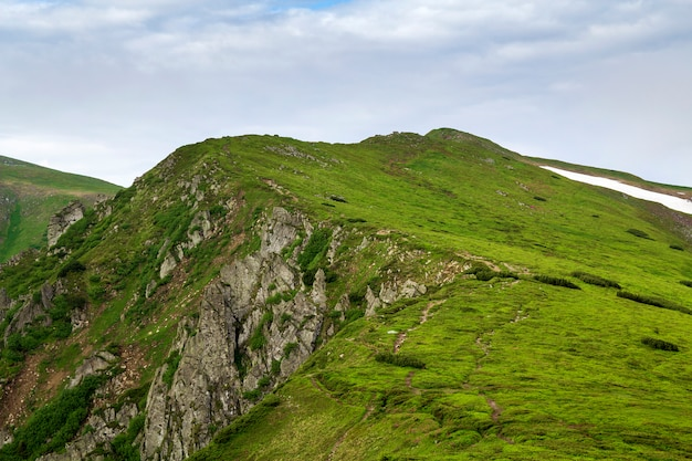 Éclairé par le soleil du matin, large vallée verte, collines couvertes d'herbe et de rochers de montagne brumeux lointains sous un ciel d'été bleu vif et des nuages blancs gonflés. beauté de la nature, du tourisme et du concept de voyage.