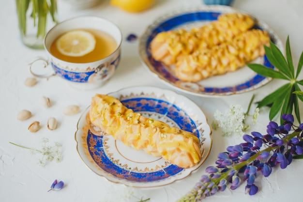 Éclairs au citron et thé au citron dans un service à thé vintage et fleurs sur blanc