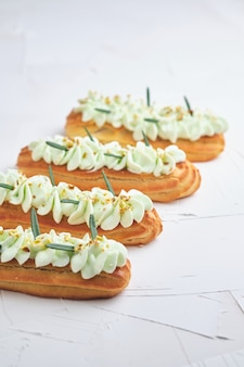 Eclairs à la crème de pistache et garniture à la framboise, garnis de pistaches concassées et de romarin.