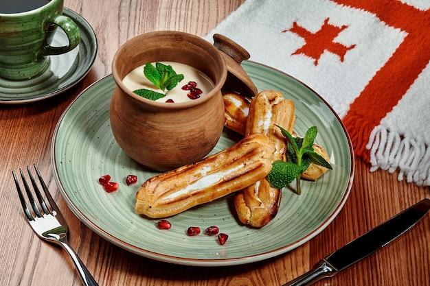Eclairs délicats de pâte à choux avec garniture à la crème aromatisée servis avec du matsoni garni de graines de grenade et de menthe fraîche dans un restaurant géorgien sur une table en bois sur fond de drapeau national