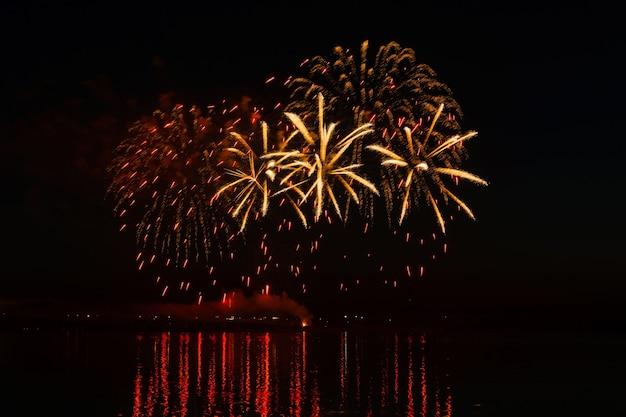 Des éclairs de feux d'artifice festifs au-dessus de la rivière nocturne se reflètent dans l'eau