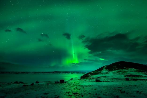 Des éclairs de lumière dans une aurore boréale sur un lac gelé de l'île