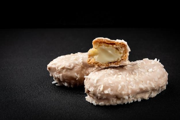 Éclairs de noix de coco ou biscuits à la crème sur fond noir.