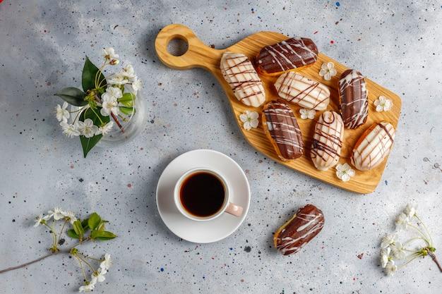 Eclairs ou profiteroles au chocolat noir et chocolat blanc avec de la crème anglaise à l'intérieur, dessert français traditionnel.vue d'en haut.