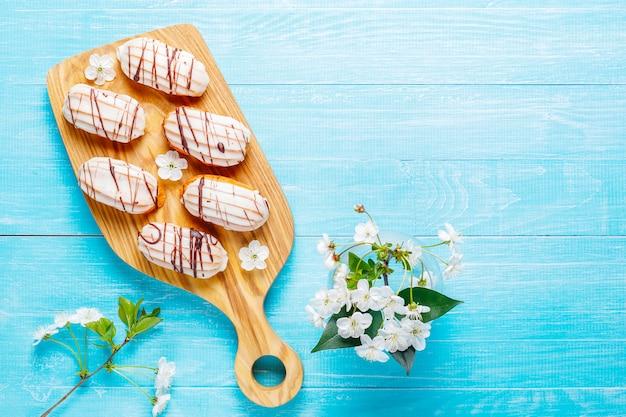 Eclairs ou profiteroles au chocolat noir et chocolat blanc avec crème pâtissière à l'intérieur, dessert français traditionnel.