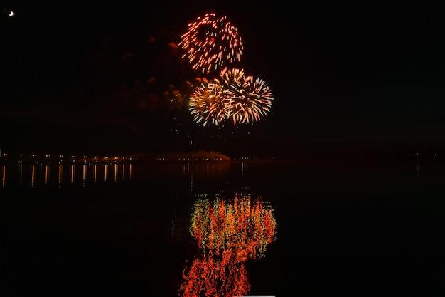 Des éclairs de salut festif au-dessus de la rivière nocturne se reflètent dans l'eau