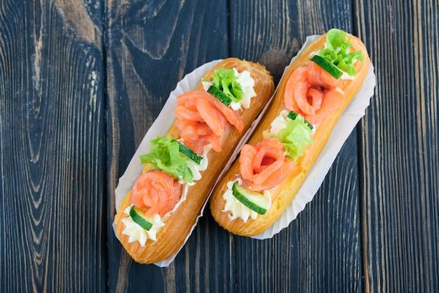 Des éclairs savoureux et beaux sur une planche de bois. dessert appétissant avec poisson rouge, concombre, fromage et légumes verts.