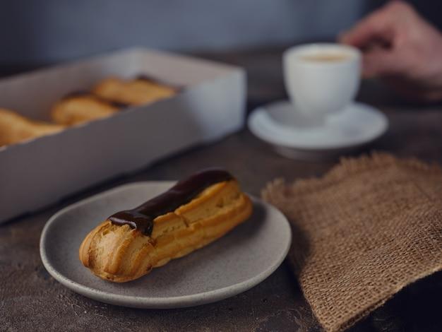 Éclairs sur la table et une tasse d'espresso