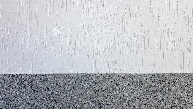 Éclats de marbre gris et stuc léger décoratif sur le mur divisé par une ligne horizontale. fond de façade de bâtiment. texture de stuc dans la rue.