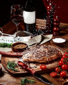 Des éclats de sel tombent sur un steak de bœuf servi avec du vin