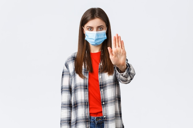 Éclosion de coronavirus, loisirs en quarantaine, concept de distanciation sociale et d'émotions. arrêtez de propager le covid-19 restez à la maison. une jeune femme sérieuse tend la main dans l'interdiction, la restriction ou l'avertissement