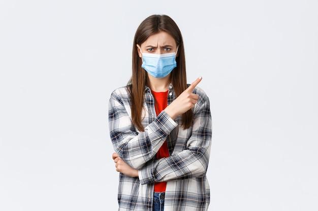 Éclosion de coronavirus, loisirs en quarantaine, concept de distanciation sociale et d'émotions. jeune femme en colère et déçue, confuse, pointant le doigt dans le coin supérieur droit en fronçant les sourcils, porte un masque