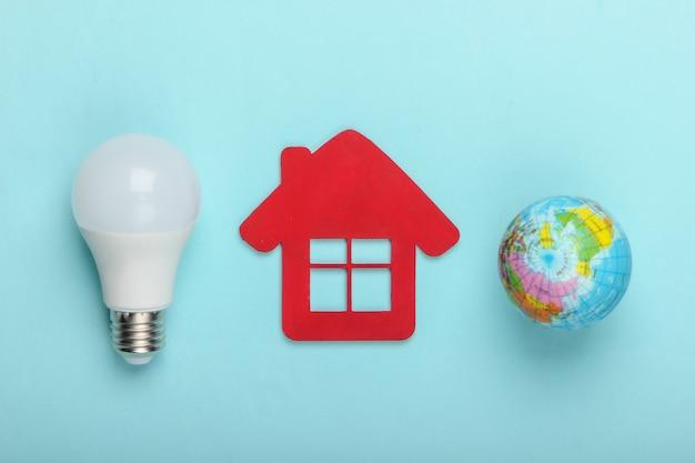 Eco, concept d'économie d'énergie. figurine de maison avec ampoule led, globe sur fond bleu pastel. vue de dessus