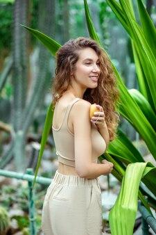 Eco. femme souriante en vêtements beiges tenant une barre de savon orange