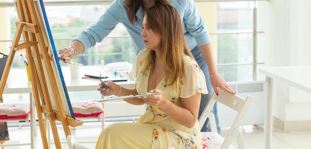 École d'art, collège des arts, éducation pour groupe de jeunes étudiants. heureuse jeune femme souriante, fille apprenant à peindre avec l'enseignant.