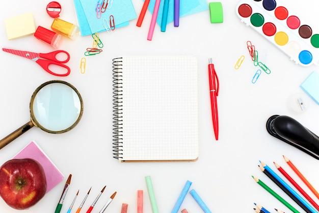 École avec cahiers, crayons, pinceau, ciseaux et pomme sur blanc
